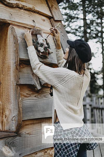 Junge Frau schmückt Holzhaus mit Weihnachtsdekoration
