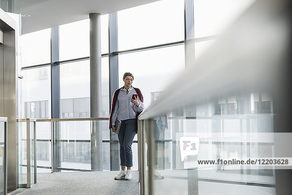 Junge Frau am Fenster stehend mit dem Handy