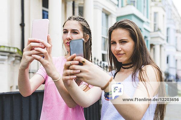 Zwei Teenager-Mädchen in der Stadt  die nebeneinander stehen und sich selbst nehmen.