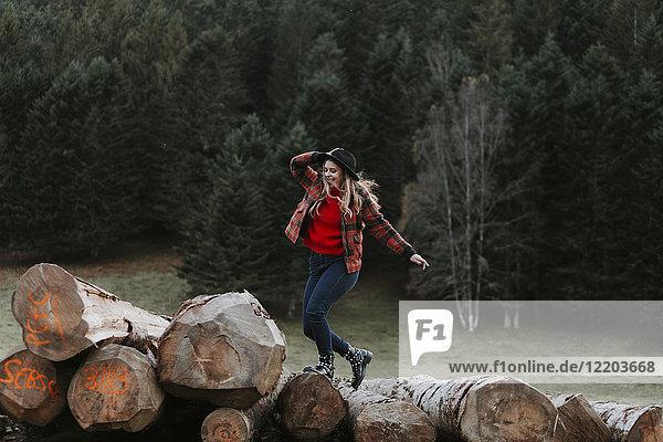 Junge Frau balanciert auf Baumstämmen