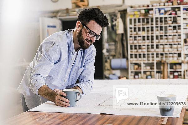 Lächelnder Mann schaut auf den Bauplan