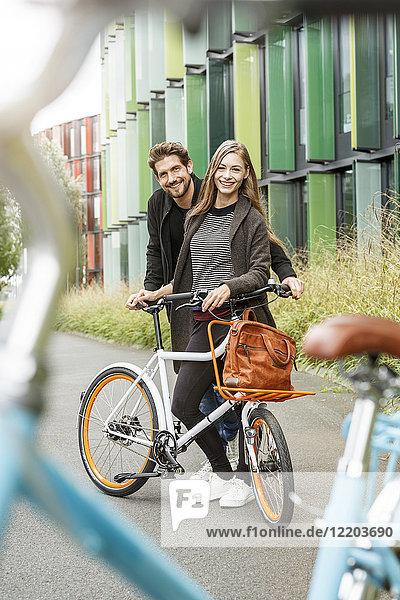 Porträt eines lächelnden Paares mit Fahrrad auf einem Weg