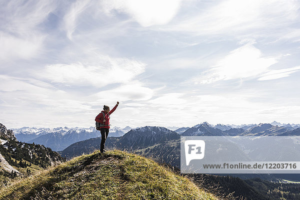 Austria  Tyrol  young woman standing in mountainscape cheering