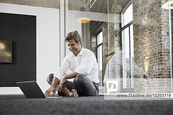 Barfuß Geschäftsmann mit Laptop auf dem Boden im modernen Büro