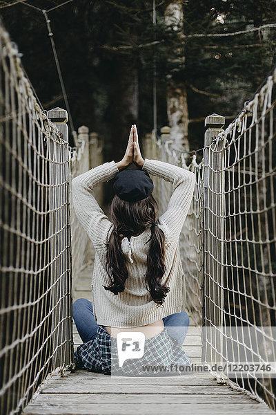 Junge Frau in Yoga-Pose auf einer Hängebrücke sitzend