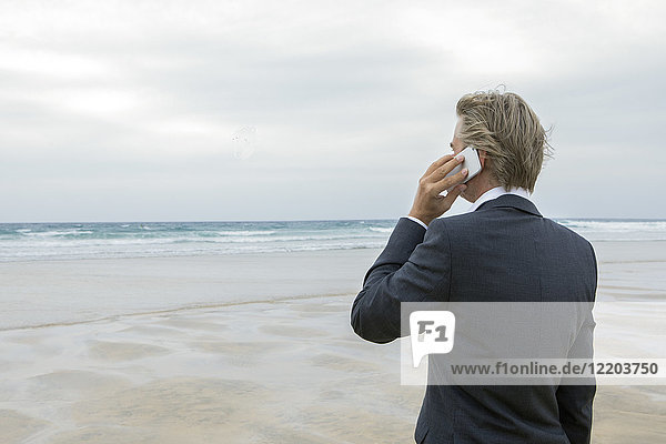 UK  Cornwall  Hayle  businessman on the beach talking on cell phone
