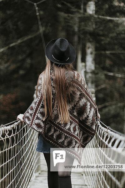 Rückansicht der modischen jungen Frau mit Hut und Poncho auf der Hängebrücke