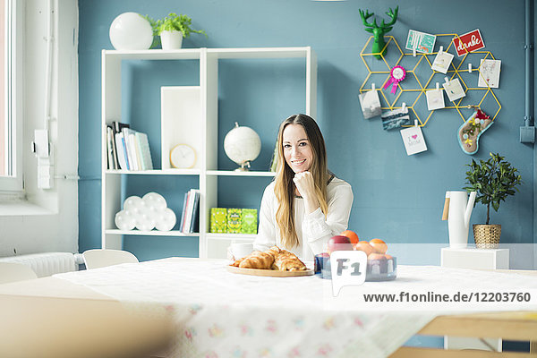 Portrait of smiling woman sitting at breakfast table
