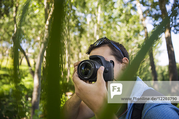 Man taking photos in forest