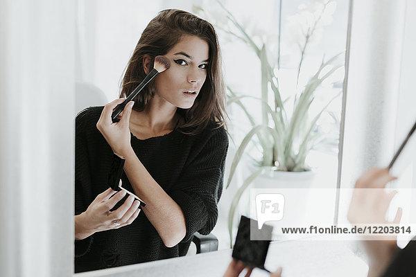 Mirror image of young woman applying Makeup