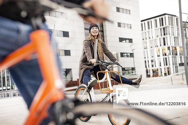 Sorgenfreie Frau mit Mann auf dem Fahrrad in der Stadt Sorgenfreie Frau mit Mann auf dem Fahrrad in der Stadt