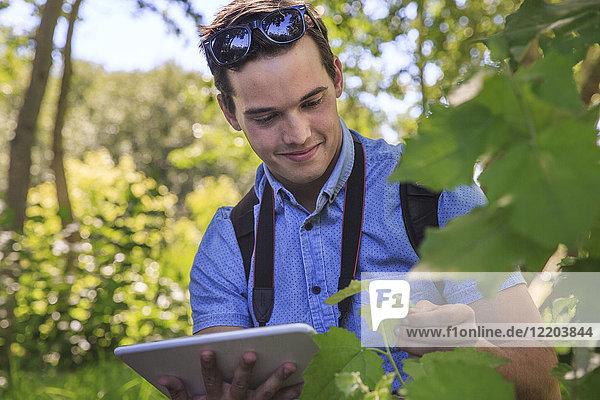 Portrait of relaxed man using tablet in nature