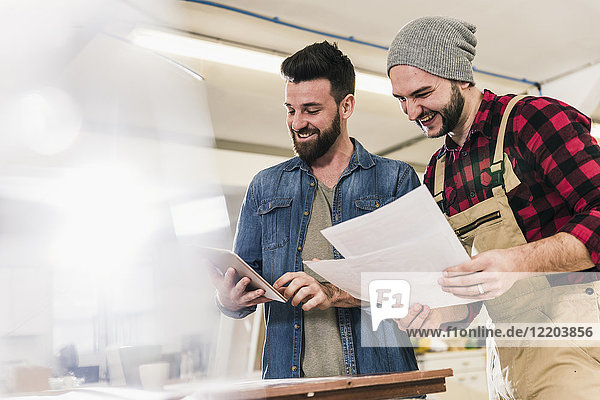 Zwei glückliche Männer mit Tablette beim Betrachten des Entwurfs in der Werkstatt