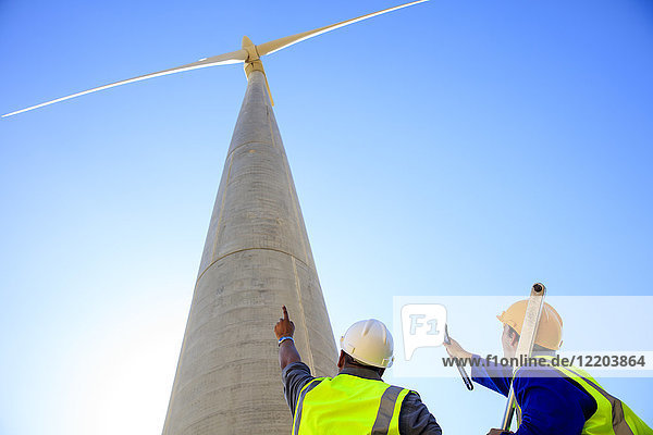 Low angle view of technicians in front of wind turbine