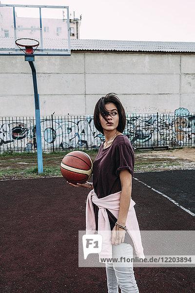 Junge Frau stehend mit Basketball auf dem Außenplatz