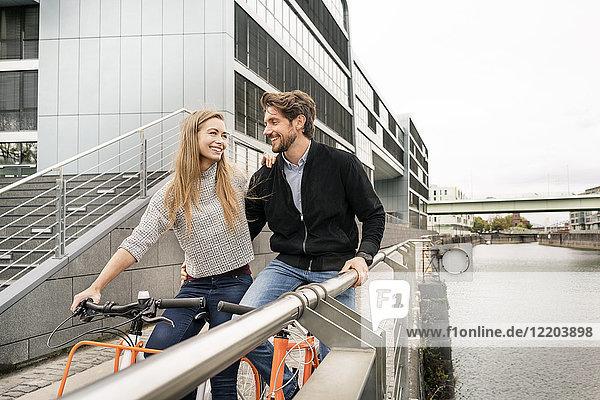 Lächelndes Paar mit Fahrrädern in der Stadt