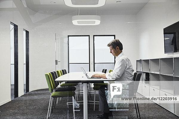 Ausgereifter Geschäftsmann im modernen Konferenzraum mit Laptop