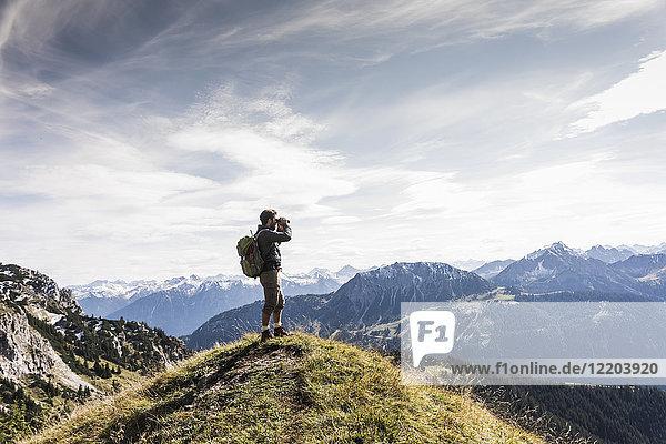 Österreich  Tirol  junger Mann steht in der Berglandschaft und schaut mit dem Fernglas in die Ferne.