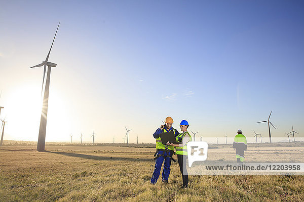 Three engineers with laptop on a wind farm