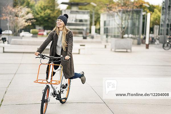 Glückliche Frau beim Fahrradfahren in der Stadt