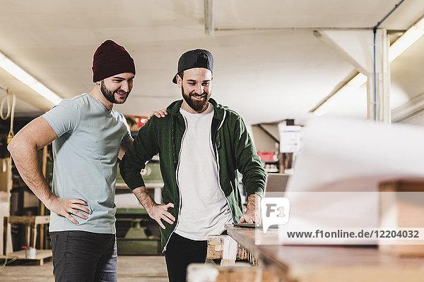 Zwei lächelnde junge Männer beim Blick auf den Laptop in der Werkstatt