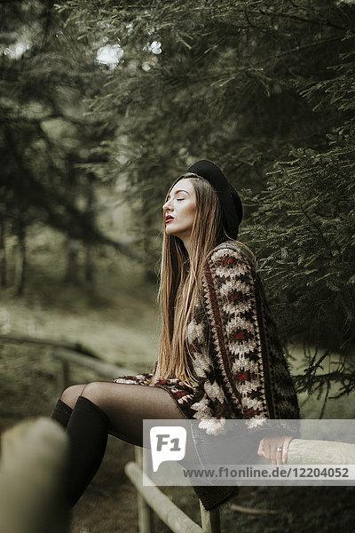 Modische junge Frau entspannt im Wald