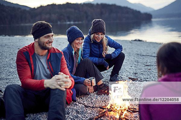 Lächelnde Freunde sitzen am Lagerfeuer am Seeufer