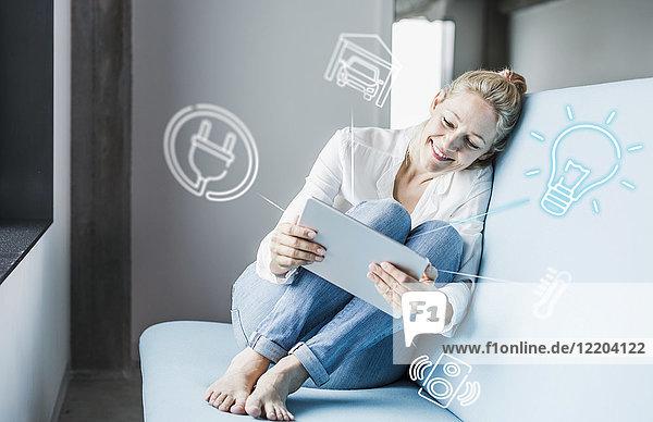 Frau sitzt im Büro und benutzt ein digitales Tablett  um sein intelligentes Zuhause fernzusteuern.