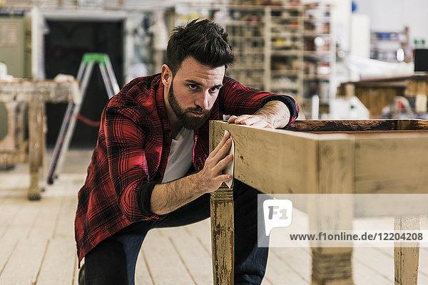 Mann behandelt Holz in der Werkstatt mit Schleifpapier