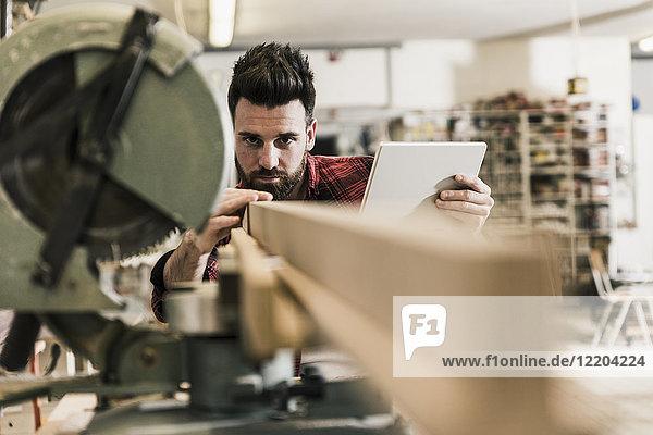 Mann in der Werkstatt mit Holzstück und Tablette