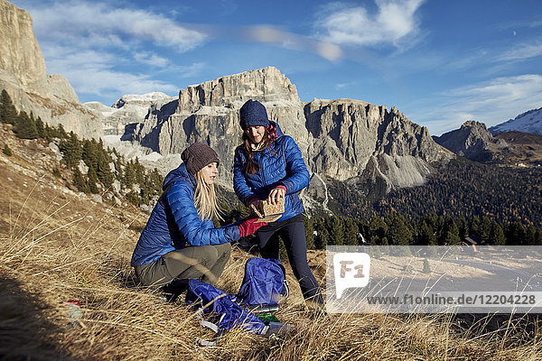 Two young women hiking in the mountains having a break