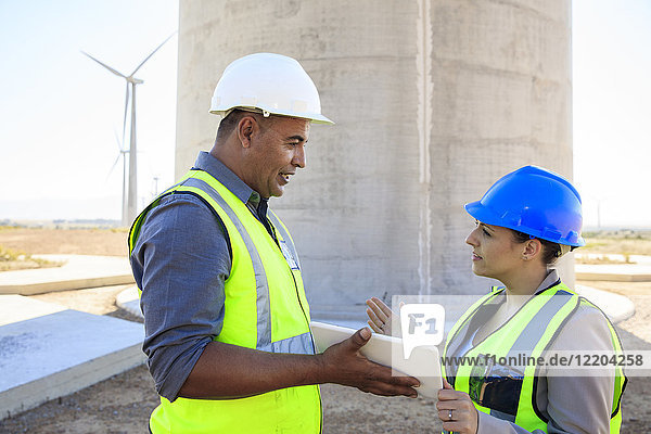 Two engineers with tablet discussing on a wind farm
