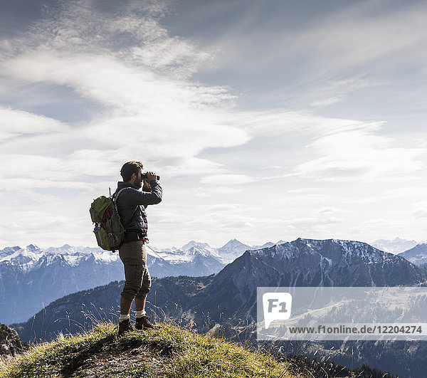 Austria  Tyrol  young man standing in mountainscape looking at view with binoculars