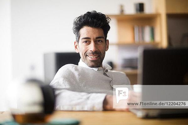 Porträt eines entspannten Geschäftsmannes am Schreibtisch