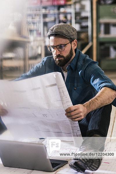 Mann auf dem Boden sitzend mit Blick auf den Bauplan