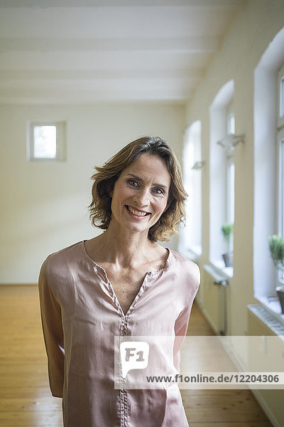 Portrait of smiling mature woman in empty room