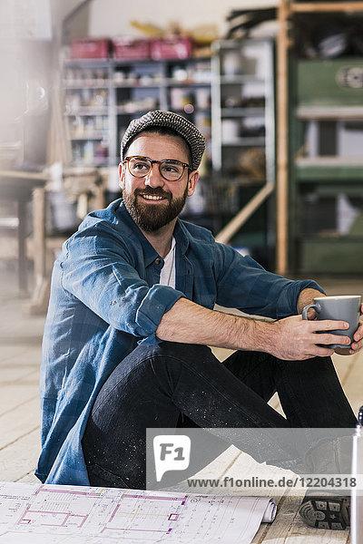 Lächelnder Mann mit Tasse Kaffee und Bauplan auf dem Boden sitzend