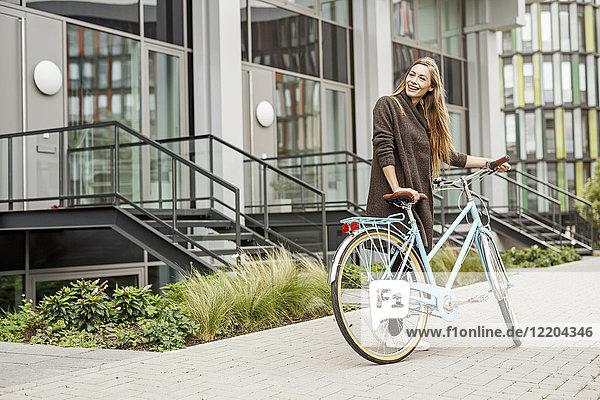 Lächelnde Frau mit Fahrrad vor einem Gebäude stehend