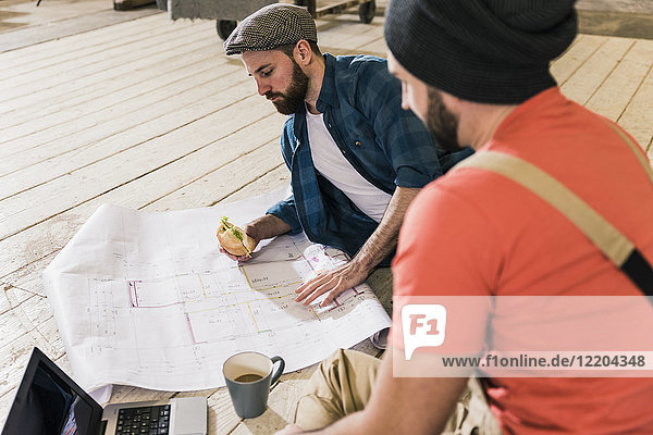 Zwei Männer mit Laptop beim Betrachten des Bauplans auf dem Boden