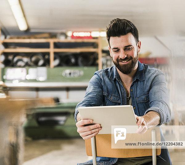 Lächelnder Mann sitzt auf Stuhl in der Werkstatt