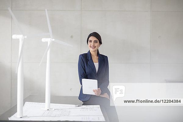 Porträt einer lächelnden jungen Frau mit Bauplan  Windkraftanlagenmodellen und Tablette im Büro