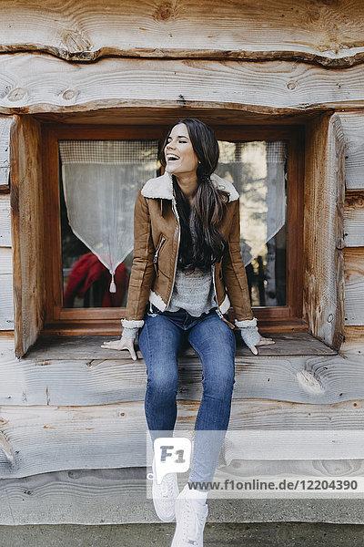 Glückliche junge Frau sitzt auf der Fensterbank eines Holzhauses