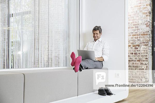 Geschäftsmann mit rosa Socken mit Laptop im Büro