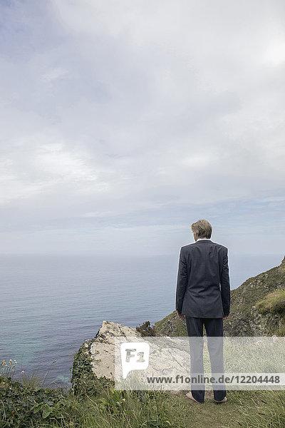 UK  Cornwall  Gwithian  Geschäftsmann an der Küste stehend mit Blick auf die Küste