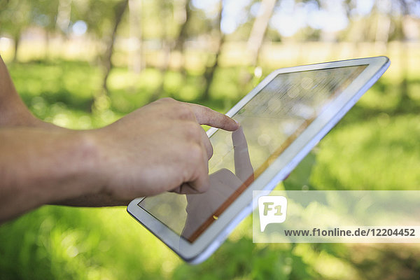 Hand of man using tablet outdoors