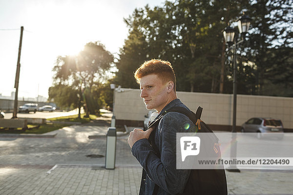 Redheaded young man outdoors on the street