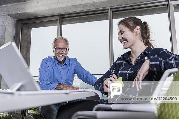 Lächelnder reifer Geschäftsmann und junge Frau mit Tablette im Konferenzraum im Büro
