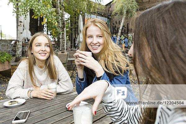 Deutschland  Berlin  Gruppe von drei Freunden beim Kaffeetrinken im Straßencafé