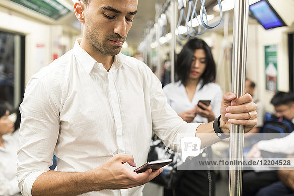 Geschäftsmann und Geschäftsfrau mit Mobiltelefonen in der U-Bahn
