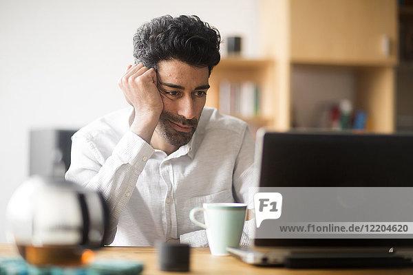 Portrait des Geschäftsmannes am Schreibtisch mit Blick auf den Laptop
